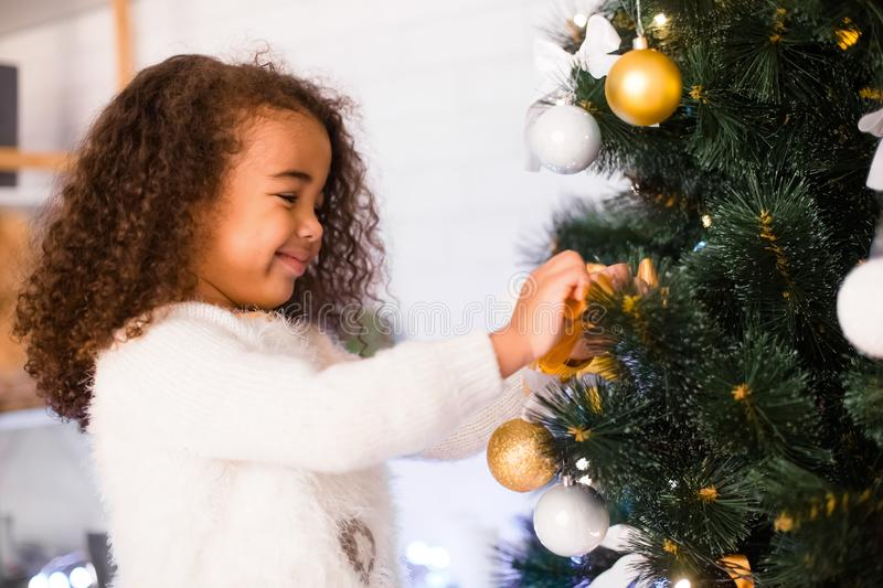 Cute african american girl decorating Christmas tree stock photography