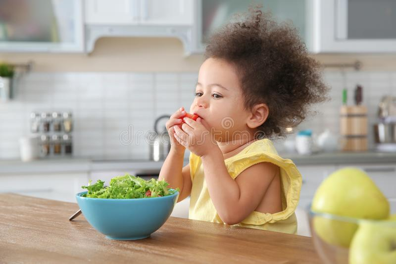 Cute African-American girl eating vegetable salad at table royalty free stock photography