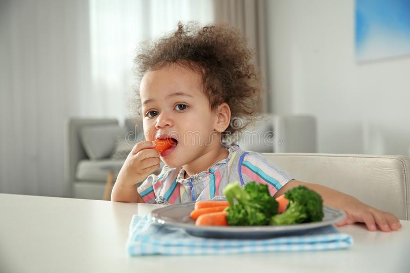 Cute African-American girl eating vegetables at table stock photography