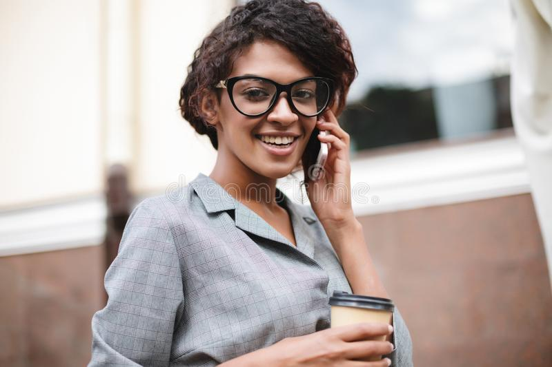 Cute African American girl in glasses standing on street and talking on her cellphone with coffee in hands. Joyful lady. Cute African American girl in glasses royalty free stock image