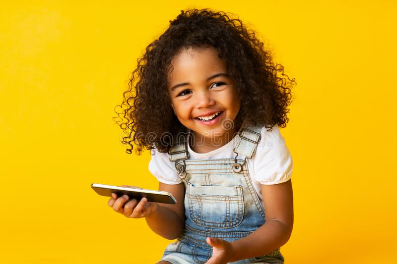 Cute african american girl holding cellphone and smiling royalty free stock photos