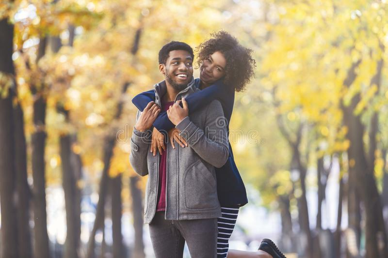 Cute black girl jumping on boyfriend back in park royalty free stock photos