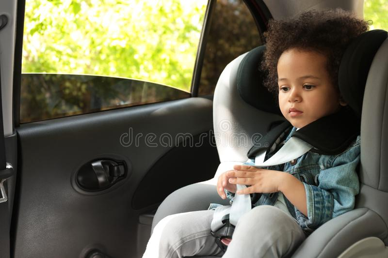 Cute African-American girl sitting in safety seat alone inside car stock images