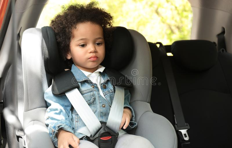 Cute African-American girl sitting in safety seat alone inside car royalty free stock photos