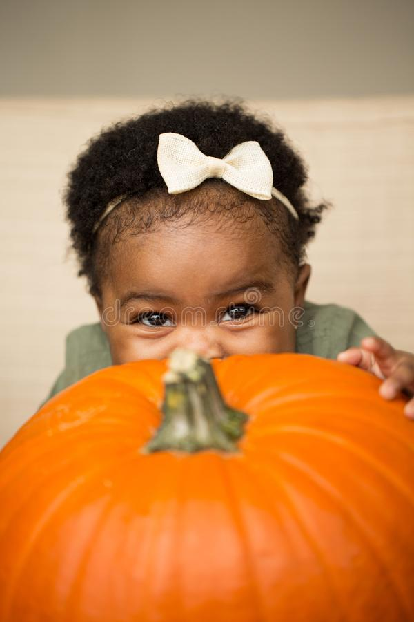 Cute African American little girl holding a pumpkin. royalty free stock images
