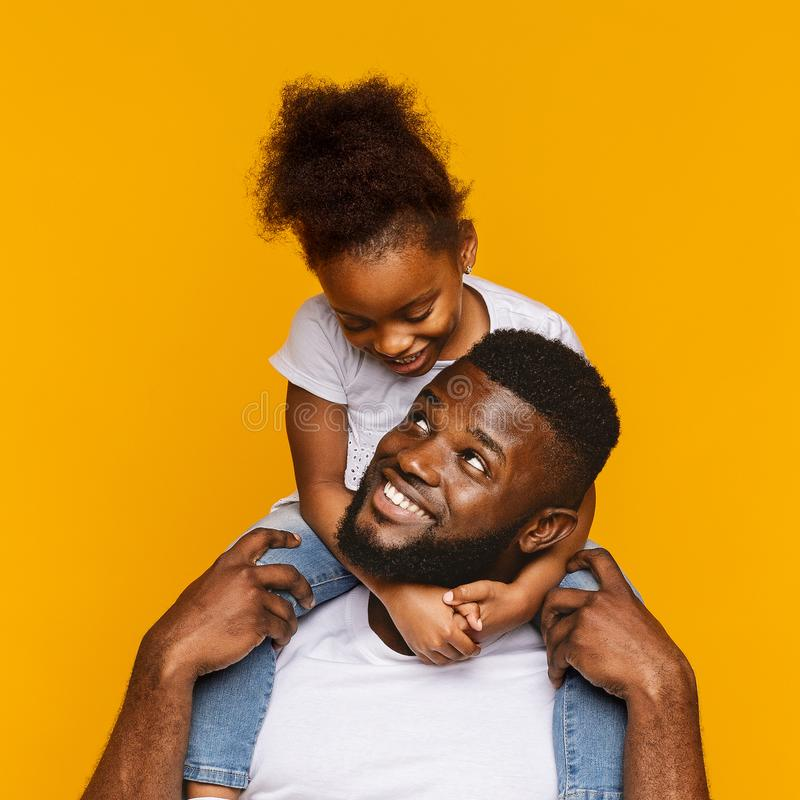 Cute african american little girl sitting on her daddy`s shoulders royalty free stock photo