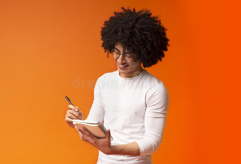 Cute african american millennial guy taking notes royalty free stock photo