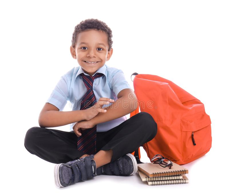 Cute African-American schoolboy with backpack on white background stock photography