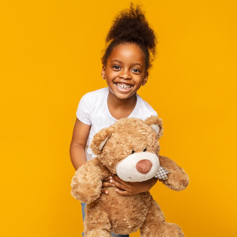 Cute african baby girl laughing with her teddy bear royalty free stock photos