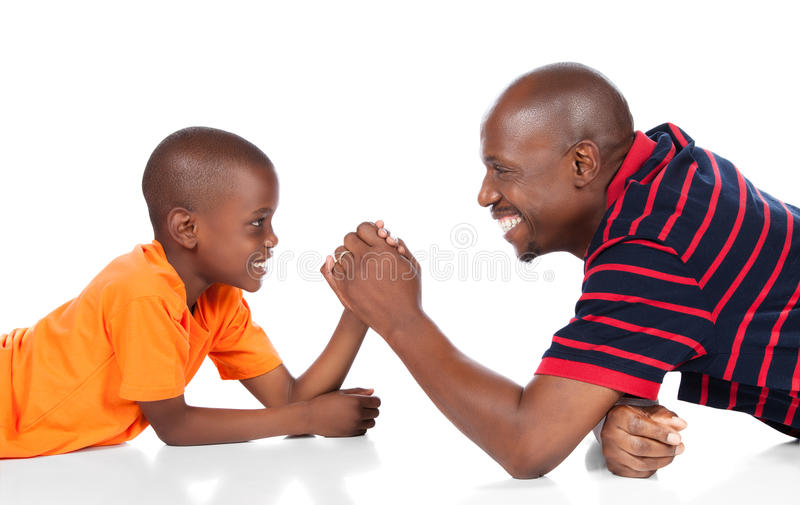Cute african boy. Wearing a bright orange t-shirt and dark denim jeans is playing arm wrestle with his father royalty free stock images