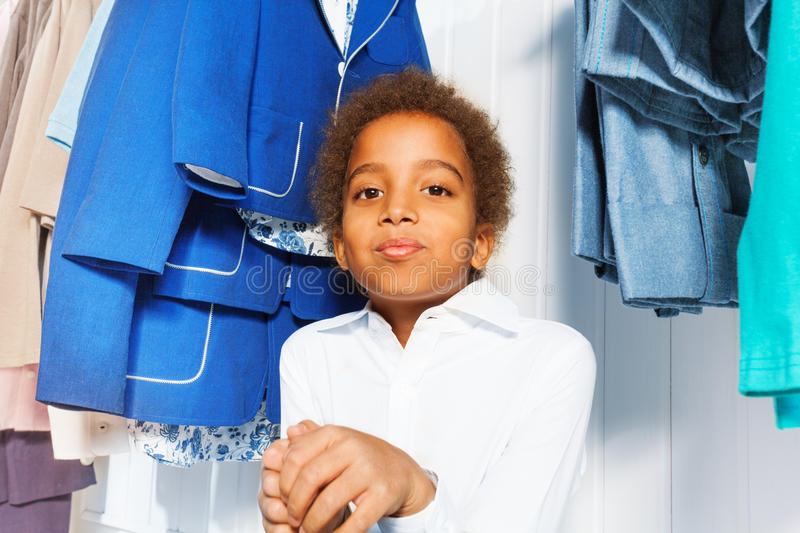 Cute African boy in white shirt sits under hangers royalty free stock photography