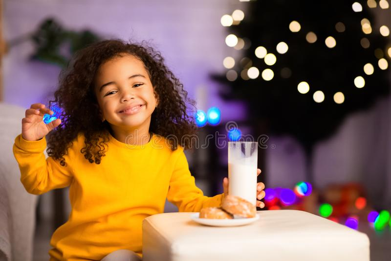 Cute african girl enjoying milk with cookies stock photo