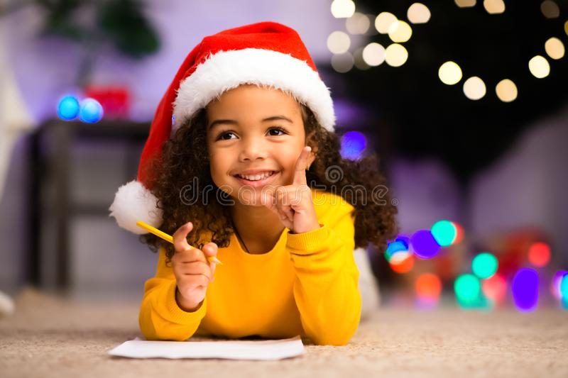 Cute african girl has great thought about Christmas gift stock photo