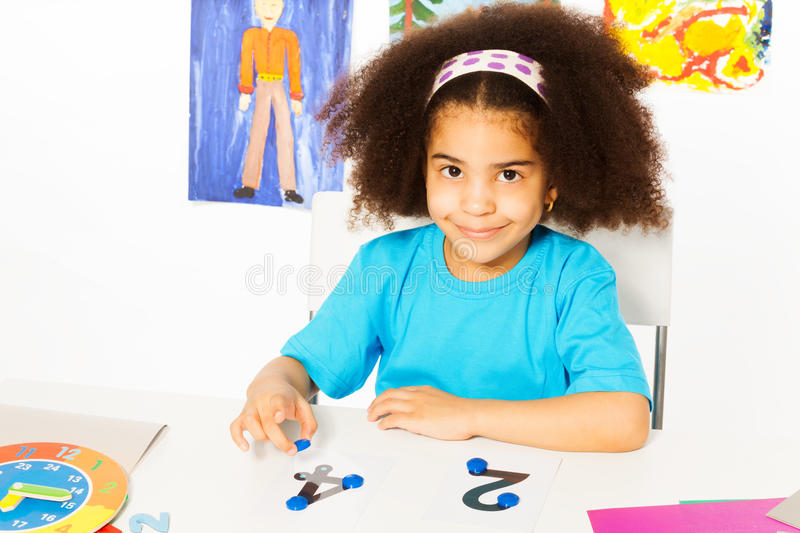 Cute African girl learn numbers with coins royalty free stock photography