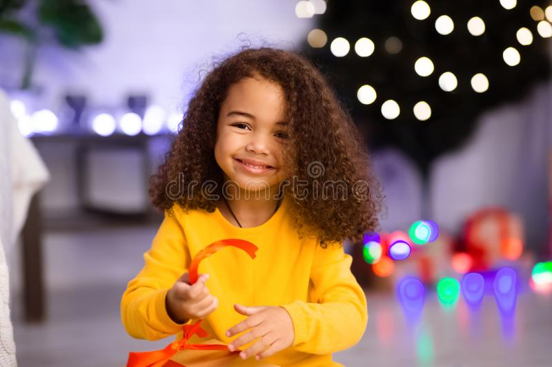 Cute african girl opening Xmas gift at home royalty free stock image