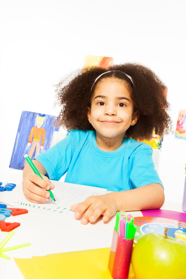 Cute African girl writing letters with pencil stock photo