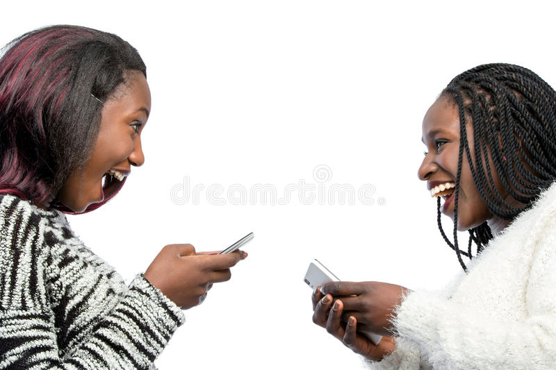 Cute african teen girls laughing with smart phones. royalty free stock image
