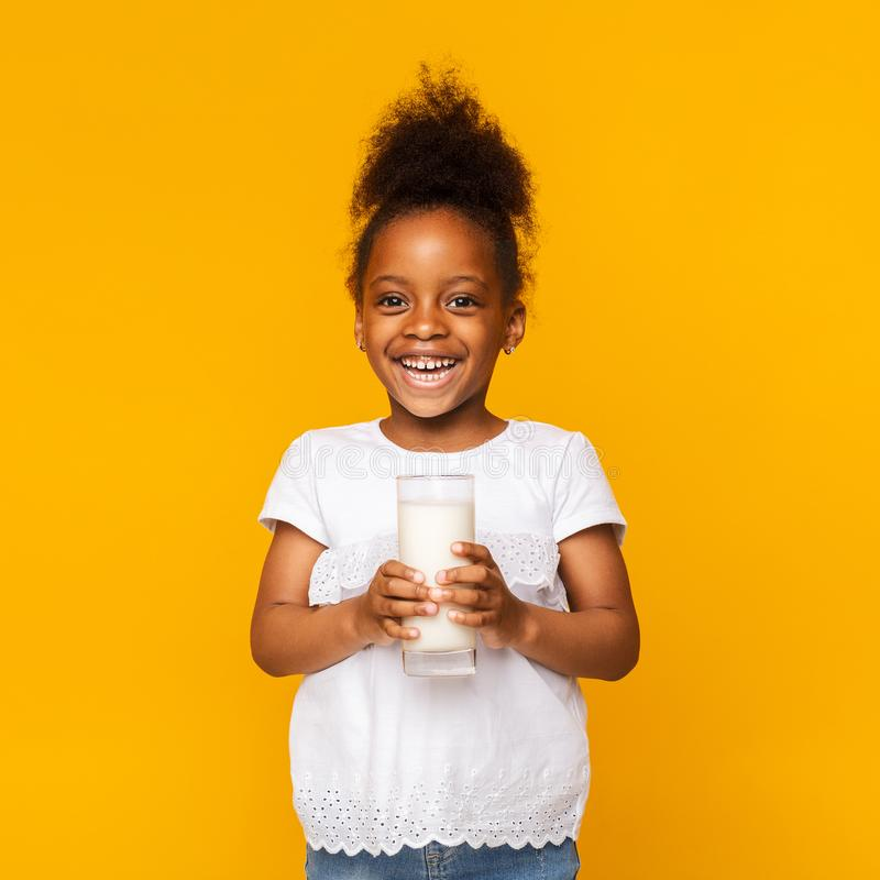 Cute afro girl enjoying glass of milk royalty free stock images