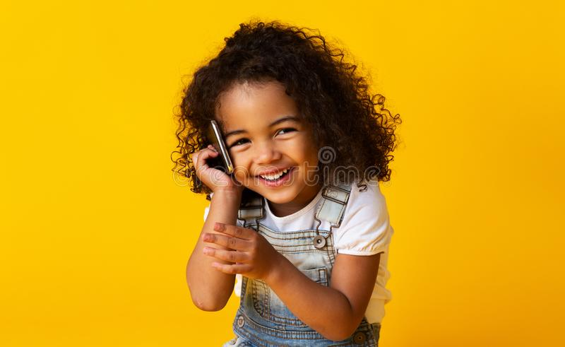 Cute afro girl talking on cellphone on yellow background royalty free stock photos
