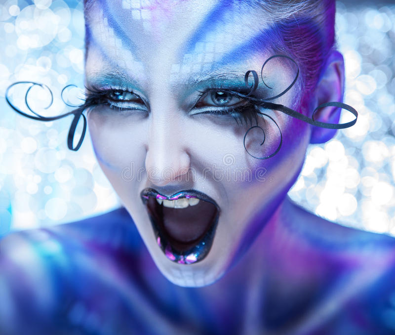 Cute and agry woman screaming. Creative make up on fashion model. Studio shot royalty free stock photography