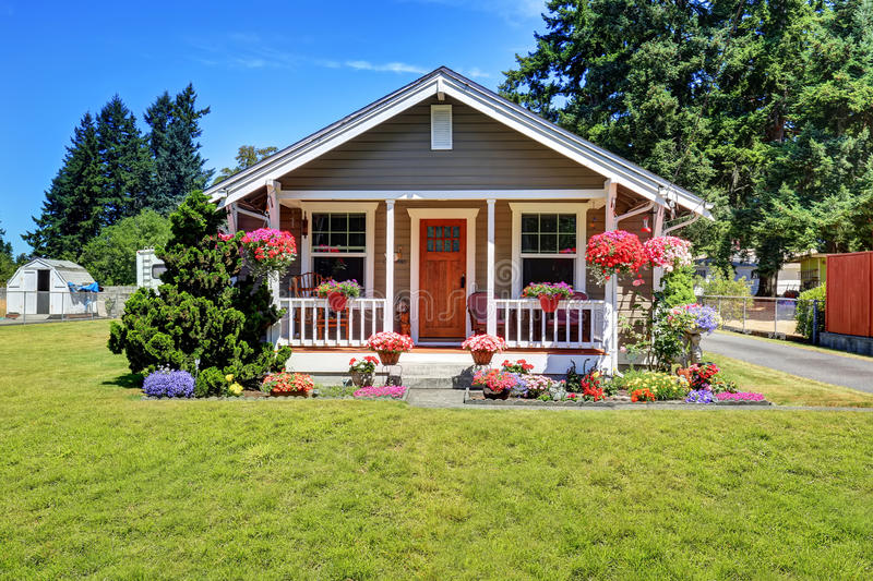 Cute American house exterior with covered porch and flower pots. Grass filled front yard. Northwest, USA royalty free stock photo