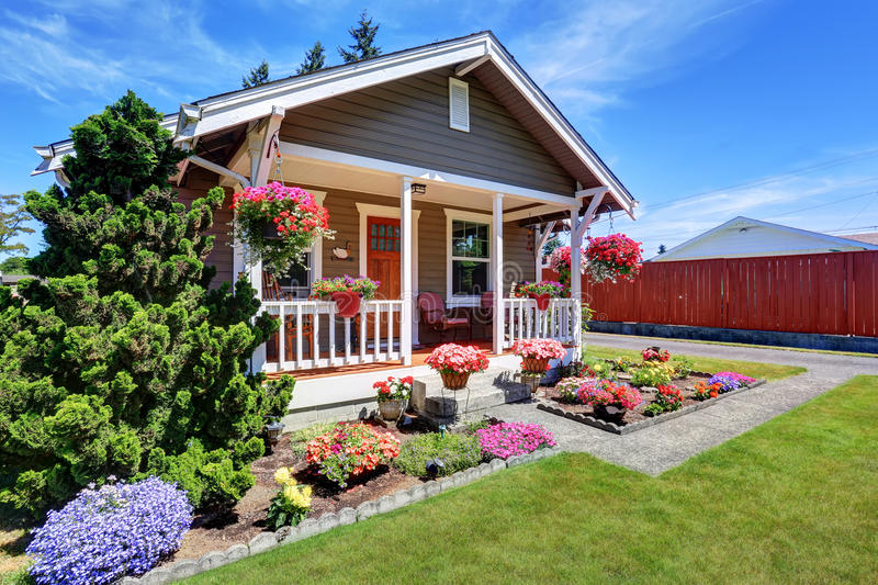 Cute American house exterior with covered porch and flower pots. Grass filled front yard. Northwest, USA stock photo