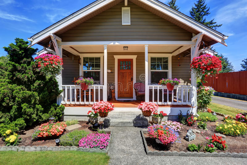 Cute American house exterior with covered porch and flower pots. Grass filled front yard. Northwest, USA royalty free stock image