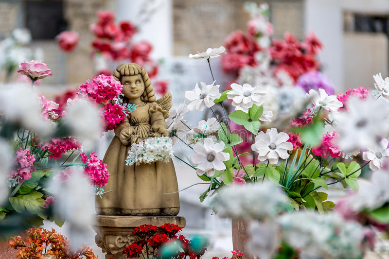 Cute angel girl statue and flowers royalty free stock photos