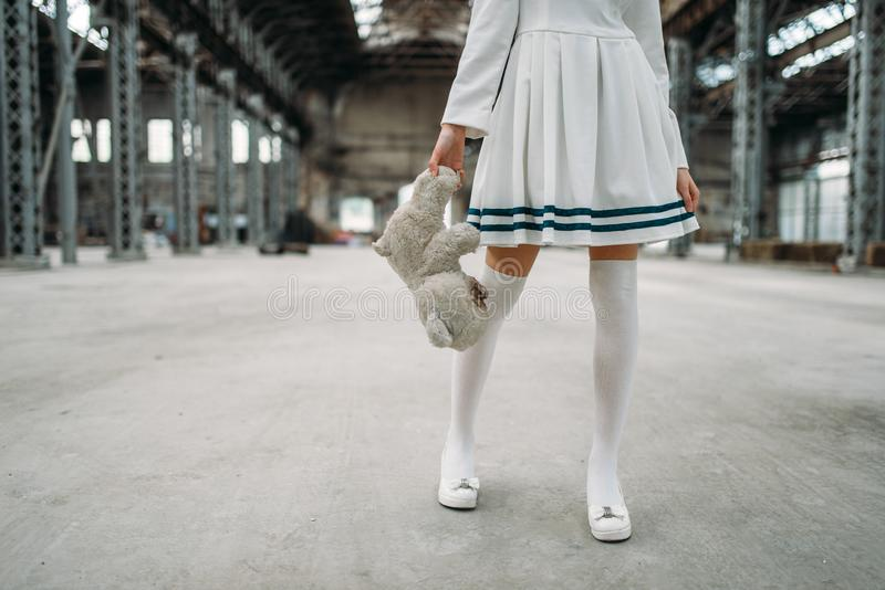 Cute anime style blonde woman with toy bear. In hand. Cosplay, japanese culture, doll in dress on abandoned factory royalty free stock images