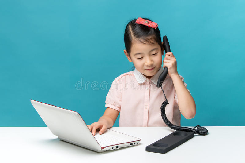Cute asia little girl is sitting at table with her white laptop. And a telephone, isolated over blue royalty free stock image