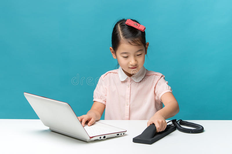 Cute asia little girl is sitting at table with her white laptop. And a telephone, isolated over blue stock photo