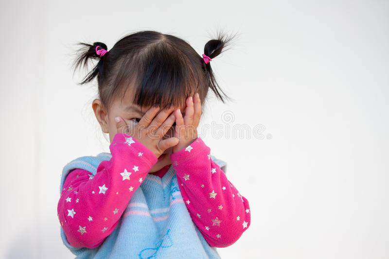 Cute asian baby girl closing her face and playing peekaboo or hide and seek. With fun stock images