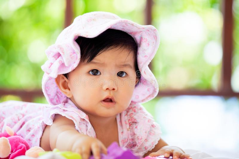 Cute asian baby girl wear pink hat crawling on blanket royalty free stock photos