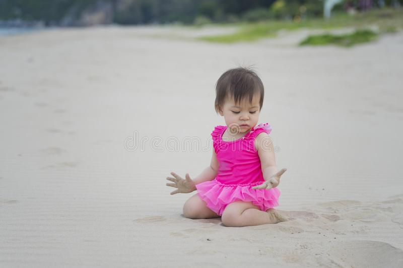 Cute Asian baby girl wearing pink color swimwear playing sands on the beach. Thailand stock photos