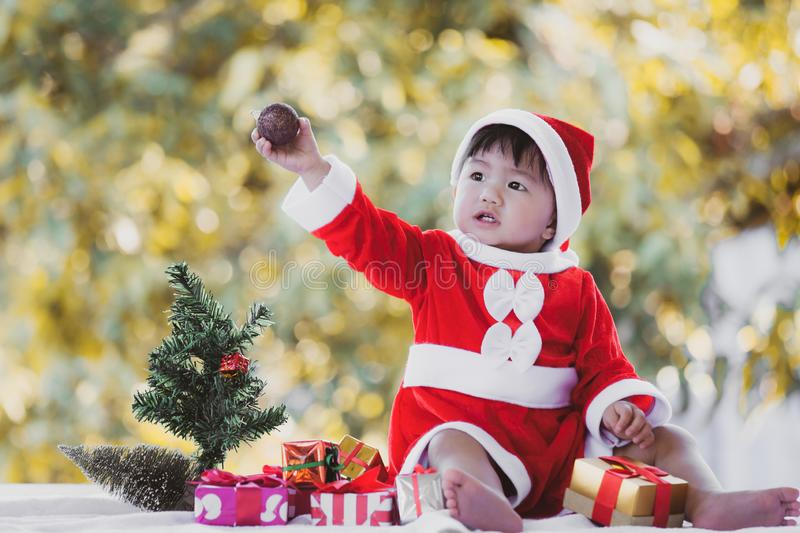 Cute asian baby girl wearing santa suit with beautiful gift boxes stock photo