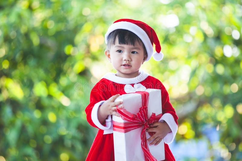 Cute asian baby girl wearing santa suit holding beautiful gift box in hand royalty free stock images
