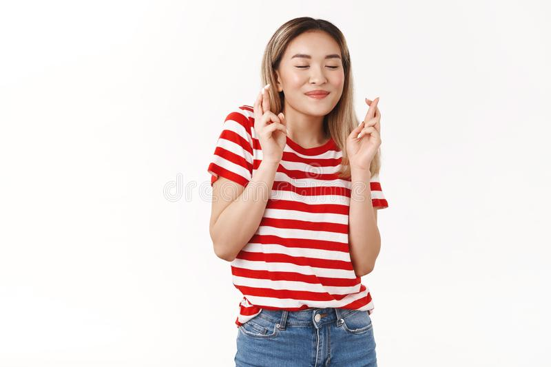 Cute asian blond female student hopes pass all exams making wish close eyes smiling dreamy cross fingers good luck. Anticipating positive results hopefully royalty free stock images