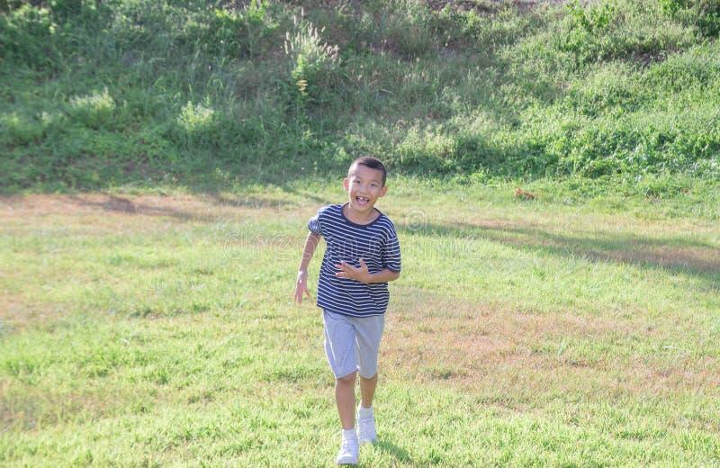 Cute asian boy running in a public park royalty free stock photos