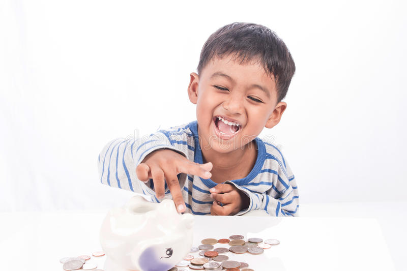 Cute asian boy saving money. In piggy bank royalty free stock photos