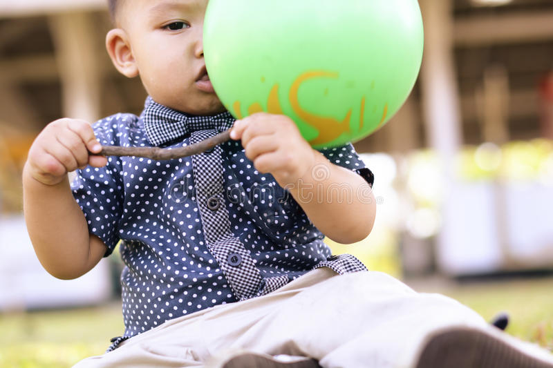 Cute asian boy sit on the ground. Green ball hit to face royalty free stock photos