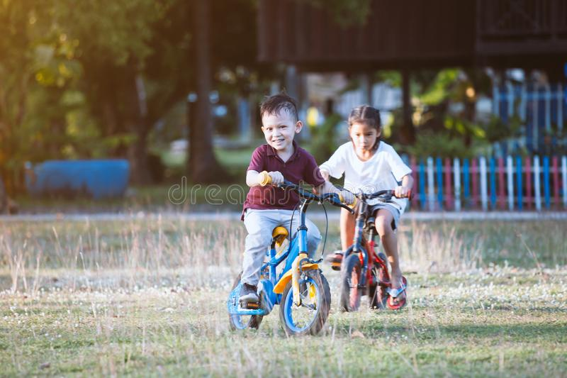 Asian child boy and his old sister having fun to ride a bicycle together in the park royalty free stock images