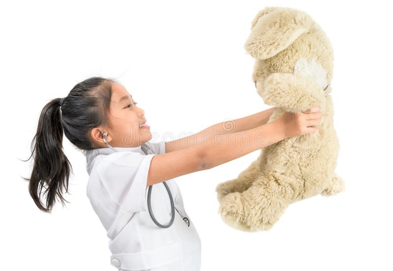 Cute asian child in doctor coat playing with teddy bear upation concept royalty free stock photo