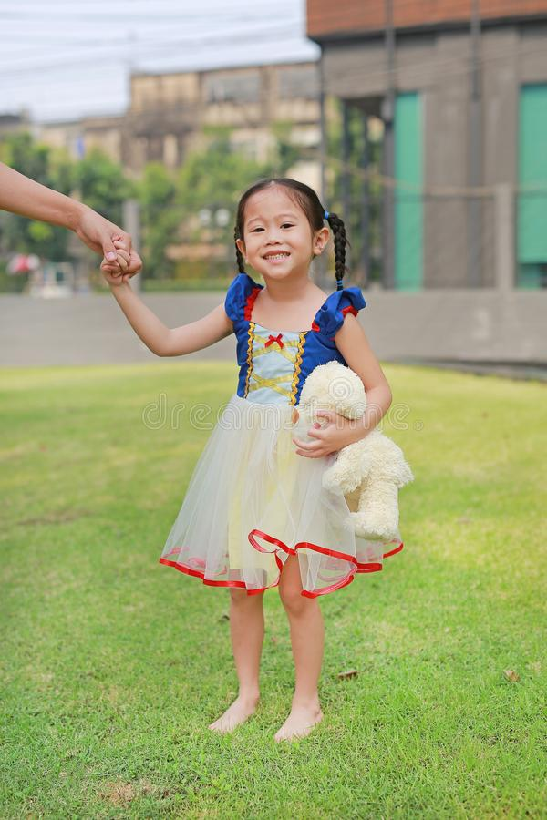 Cute Asian child girl dressed a fantasy outfit holding teddy bear and unshod walking on green grass garden with mother hand in stock photo