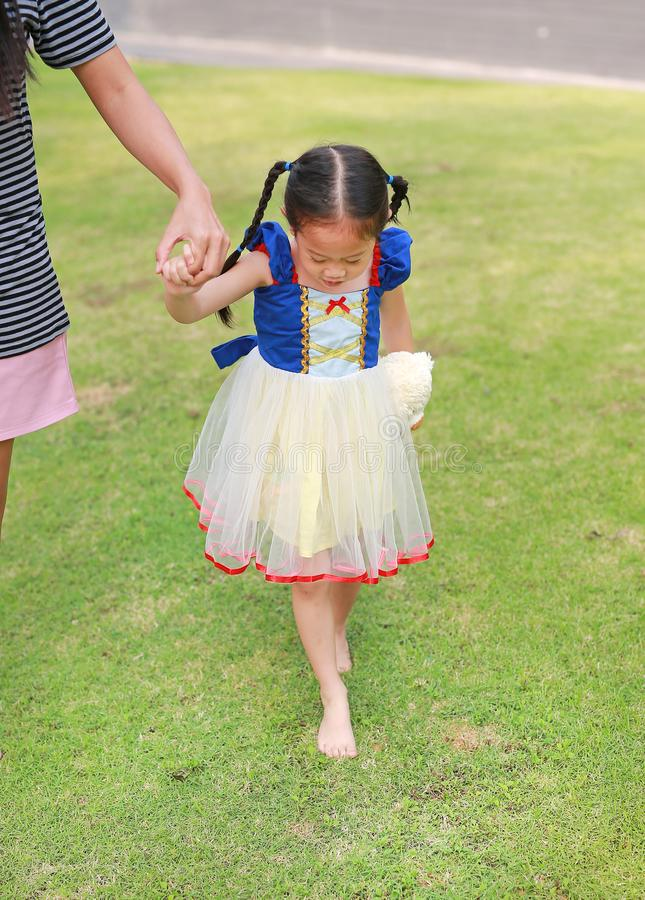 Cute Asian child girl dressed a fantasy outfit holding teddy bear and unshod walking on green grass garden with mother hand in royalty free stock images