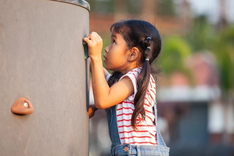 Cute asian child girl play and climbing on the rock wall royalty free stock photo
