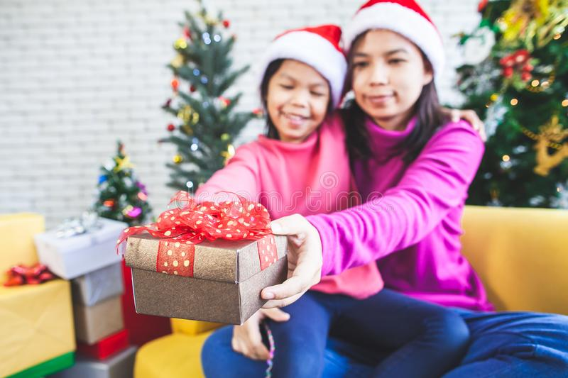 Asian child girl with her mother holding beautiful gift box and giving in Christmas celebration. Cute asian child girl with her mother holding beautiful gift box stock photography