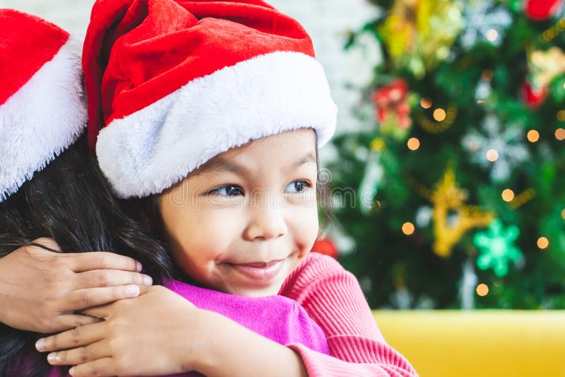 Asian child girl hugging her mother with love in Christmas celebration. Cute asian child girl hugging her mother with love in Christmas celebration royalty free stock photos