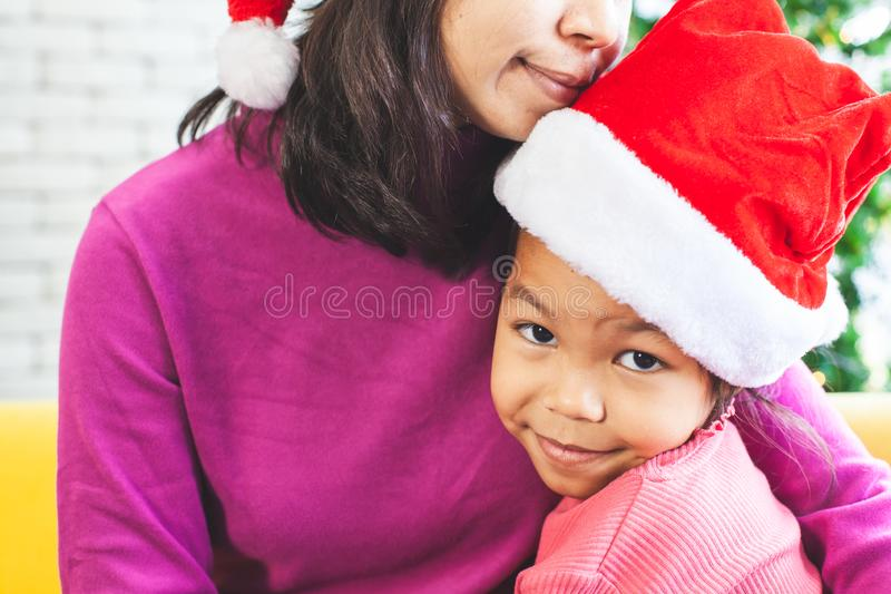 Asian child girl hugging her mother with love in Christmas celebration. Cute asian child girl hugging her mother with love in Christmas celebration stock image