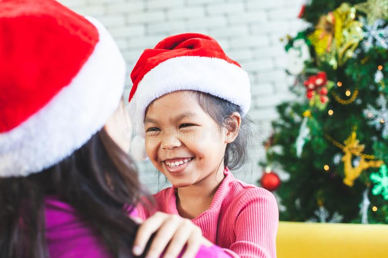 Asian child girl hugging her mother with love in Christmas celebration. Cute asian child girl hugging her mother with love in Christmas celebration stock photo