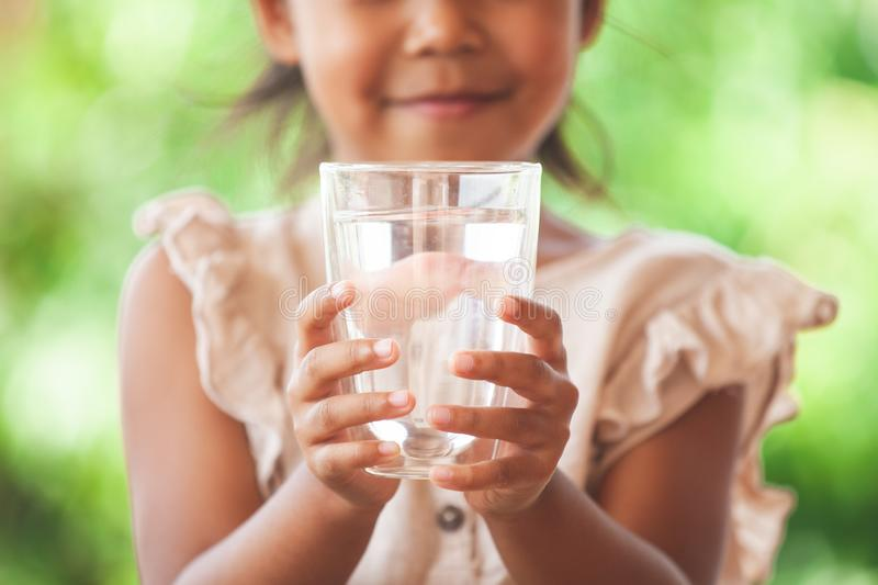Cute asian child girl like to drink water and holding glass of fresh water stock image